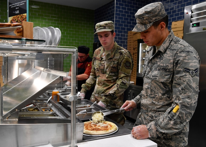 U.S. Air Force Airman 1st Class Jose Ramirez and U.S. Air Force Airman 1st Class Brett Tischner, 87th Force Support Squadron service's Airmen, make pizza for customers during the re-opening of the Halvorsen Hall Dining Facility on Joint Base McGuire-Dix-Lakehurst, New Jersey, Aug. 27, 2019. New additions to the DFAC include a pizza bar, sub sandwiches and a salad bar priced lower than food options regularly found outside of Joint Base MDL. An additional change includes utilization of the DFAC for all Joint Base MDL community members.