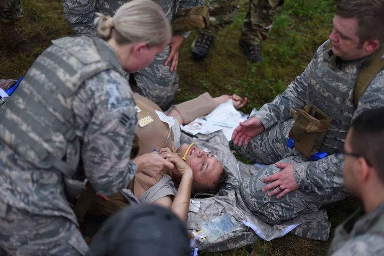 Members of the 22nd Medical Group practice using Tactical Combat Casualty Care tactics to stabilize an Airman during an Emergency Medical Technician Rodeo Aug. 22, 2019, at McConnell Air Force Base, Kan. The rodeo provided Airmen from the 22nd MDG the opportunity to perform lifesaving procedures in a simulated combat environment. This training helps identify area of improvement to develop the high-quality military essential for warfighting success. (U.S. Air Force photo by Airman 1st Class Alexi Myrick)