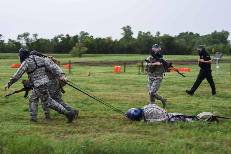 Staff Sgt. Aaron Wooton, 22nd Aerospace Medicine Squadron operational medical technician, and Airman 1st Class Anthony Thomason 22nd Healthcare Operation Squadron medical technician, drag Airman 1st Class Dylan Nealy 22nd HCOS health services management apprentice, to safety during an Emergency Medical Technician Rodeo Aug. 22, 2019, at McConnell Air Force Base, Kan. The medics practiced Tactical Combat Casualty Care tactics to effectively recover the Airman and stabilize his simulated injuries. (U.S. Air Force photo by Airman 1st Class Alexi Myrick)