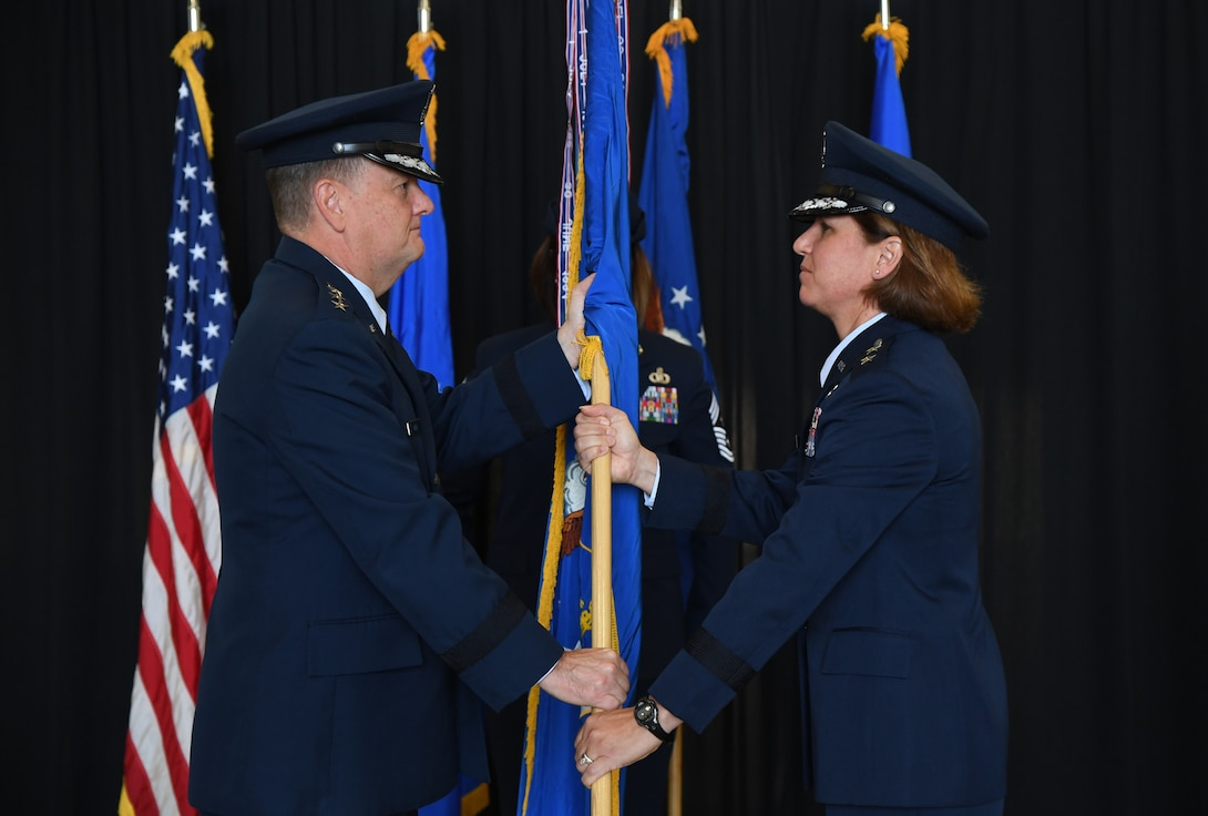U.S. Air Force Lt. Gen. Brad Webb, commander of Air Education and Training Command, passes the guidon to Maj. Gen. Andrea Tullos, Second Air Force commander, during the Second Air Force change of command ceremony on Keesler Air Force Base, Mississippi, Aug. 29, 2019. The ceremony is a symbol of command being exchanged from one commander to the next. Tullos assumed command of the Second Air Force from Maj. Gen. Timothy Leahy. (U.S. Air Force photo by Kemberly Groue)