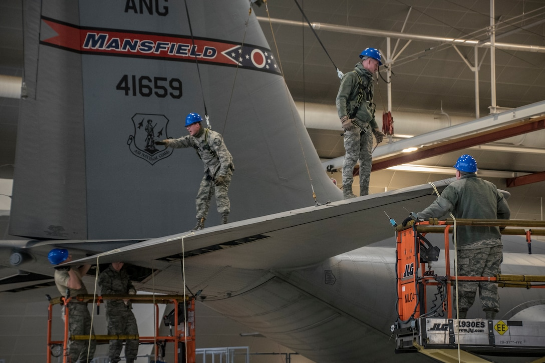 A photo of five military members walking on and around the tail of a C-130 aircraft while it was parked in the hanger.