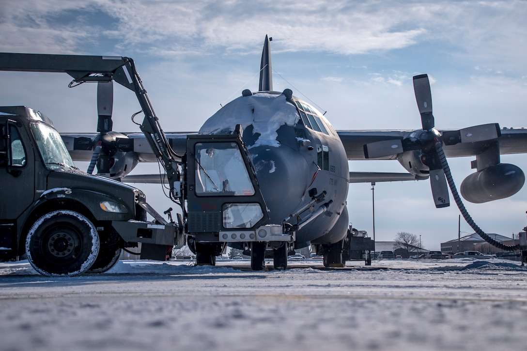 A photo of a snow covered C-130 on the flight line with military snow removal equipment.