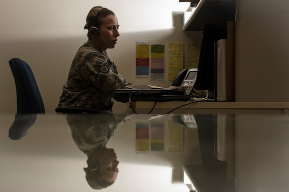 A photo of a military member and her reflections as she works on a computer.