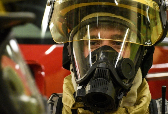 A close up photo of a firefighter with his mask and helmet on.