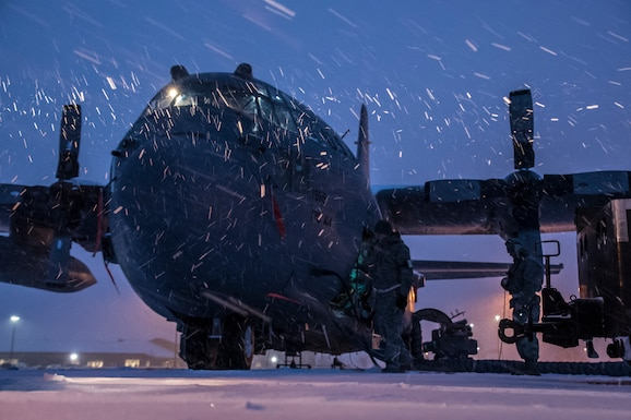 A photo of a C-130 in the early morning during a snowstorm.