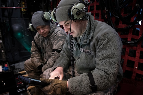 A photo of two military members viewing information on a tablet.