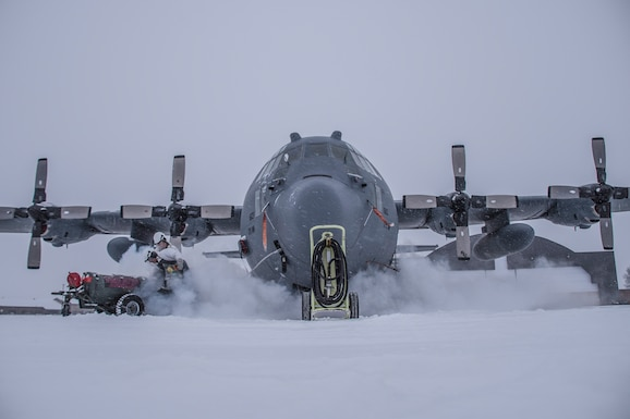 A photo of a C-130 on a snowy flight line surrounded by fog from refilling liquid oxygen.