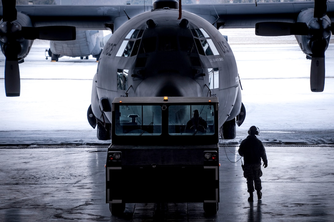 A photo of two military members pulling a C-130 aircraft into the hanger.