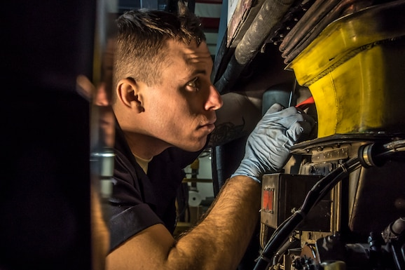 A photo of a military member working an a C-130 aircraft.
