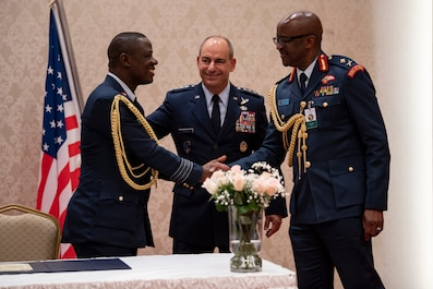 Sierra Leone Group Cpt. Hassan Coomber, Air Wing Commander, shakes hands with Kenya Maj. Gen. Francis O. Ogolla, Air Force Commander, after signing the Association of African Air Forces charter during the ninth annual African Air Chiefs Symposium at Nairobi, Kenya, Aug. 29, 2019.