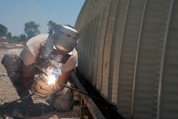 A photo of a military member using welding equipment on a military building.
