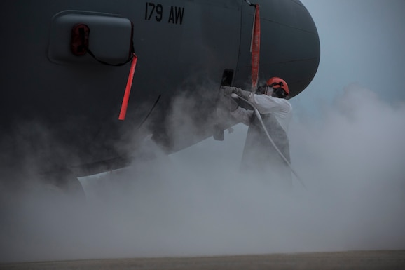 A photo of a military member surrounded by fog in front of the nose of a C-130 aircraft.
