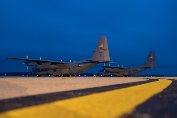 A photo of two C-130's on the flight line early morning against a dark blue sky.