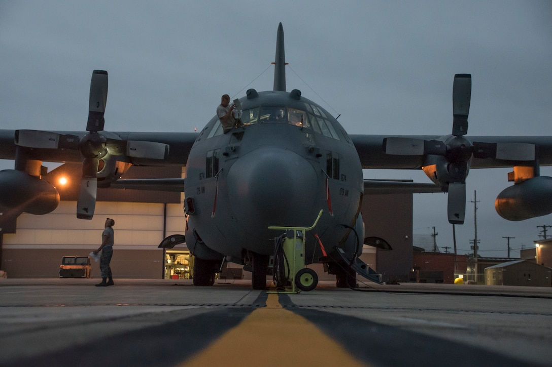 A photo of two military members working on a C-130 early morning on the flight line.