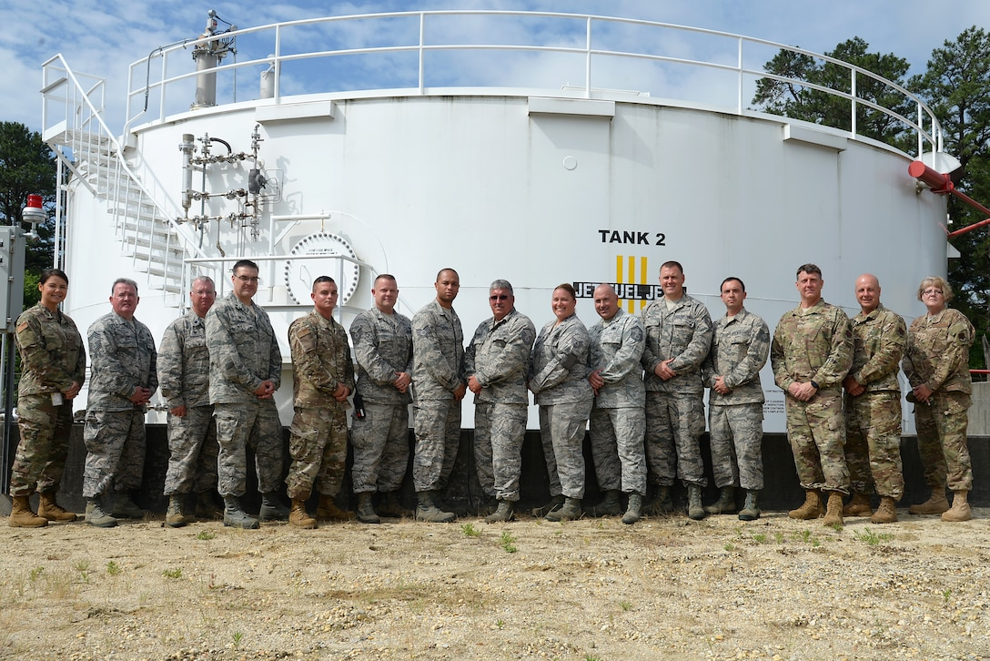 A picture of The 177th Fighter Wing Commander, Command Chief and various members of the Wing posing for a photograph in front of a jet fuel tank.