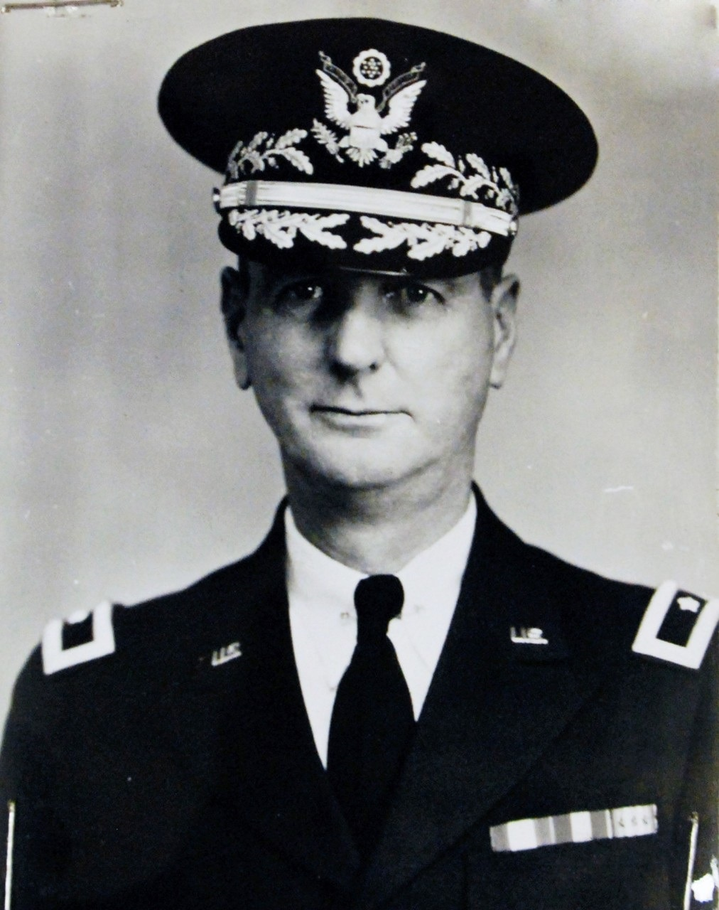 A soldier poses for a photo wearing his dress uniform and a decorated cap.