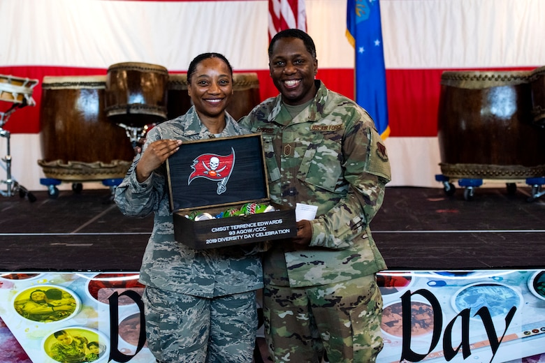 Senior Master Sgt. Melissa Wells, left, 23d Comptroller Squadron superintendent, presents a token of appreciation to Chief Master Sgt. Terrence Edwards, 93d Air Ground Operations Wing command chief, during the third annual 23d Wing Diversity Day Aug. 29, 2019, at Moody Air Force Base, Ga. Diversity Day honored the cultures of all groups and organizations observed by the Department of Defense, from LGBTQ equality to Native American heritage, and brought Airmen from across the base together to celebrate their unique differences. This year's theme was 'It's not just black and white, open your palette, create a culture of possibilities.' (U.S. Air Force photo by Senior Airman Erick Requadt)