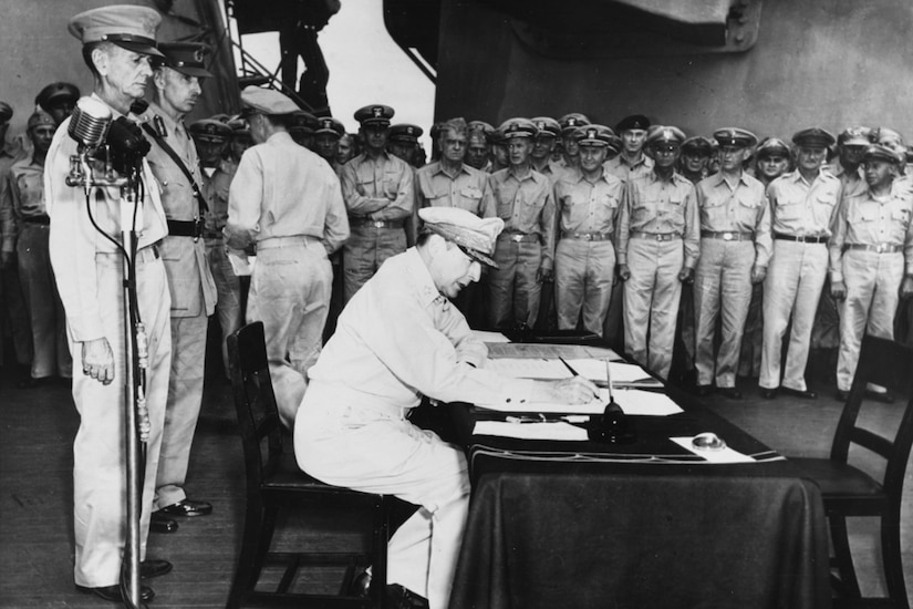 A soldier sitting in a chair at a table, signs the Japanese surrender document that ended World War II. Two other service members in dress uniform stand behind him near a microphone, and others stand off to the side.