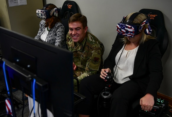 2nd Lt. Johnny Griffith, 4th Training Squadron virtual reality innovation manager, shows distinguished visitors how to fly an F-15E Strike Eagle while using a VR setup at Seymour Johnson Air Force Base, North Carolina, August 29, 2019. The DV's were part of a tour for North Carolina Governor Roy Cooper, and saw some of the innovative techniques the base is using to train its aircrew. (U.S. Air Force photo by Senior Airman Kenneth Boyton)