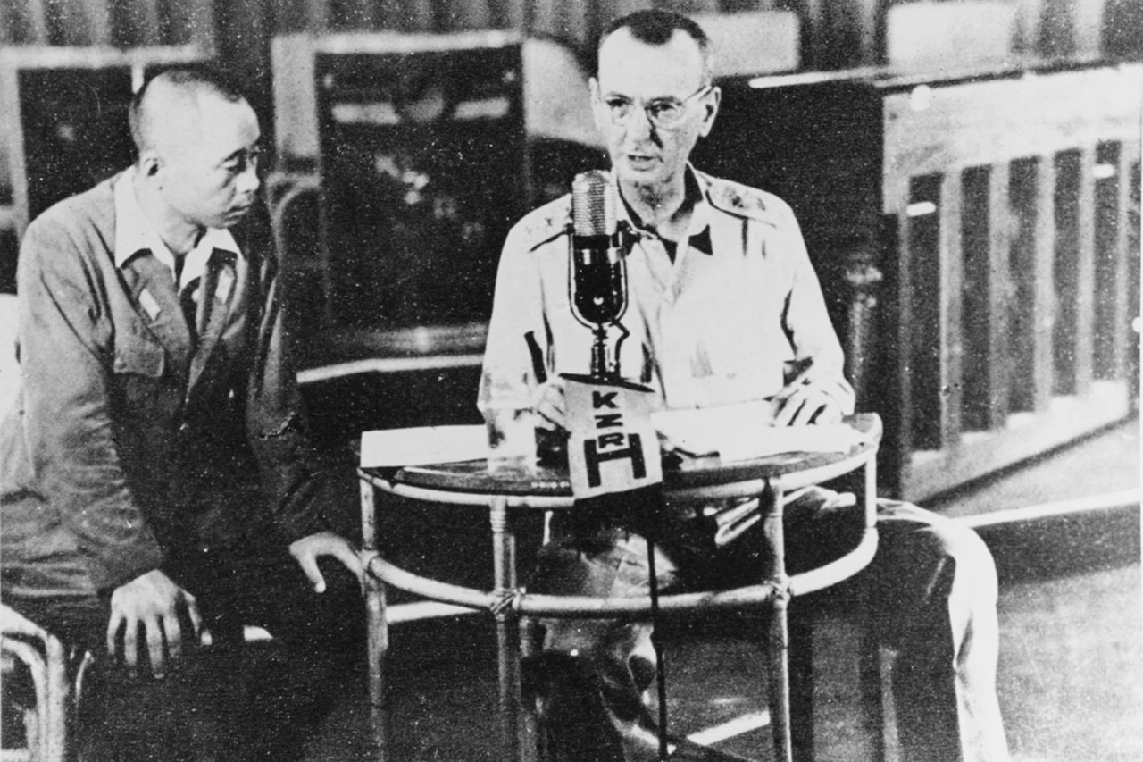 Army Lt. Gen. Jonathan Wainwright,  thin and wearing a button-down shirt and khaki pants, sits at a small table in front of a microphone as he broadcasts a message surrendering to the Japanese. A Japanese man sits beside him, looking at papers on the table.