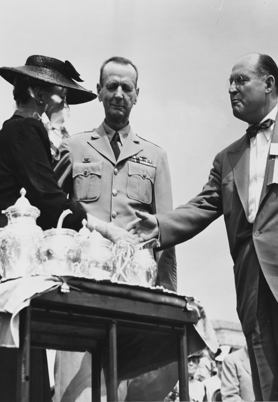 A woman wearing a hat shakes a man's hand behind a table with several tea kettles on it. A second man in uniform stands between them.
