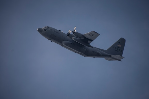 A photo of the side view of a C-130 in flight against a grey blue sky.