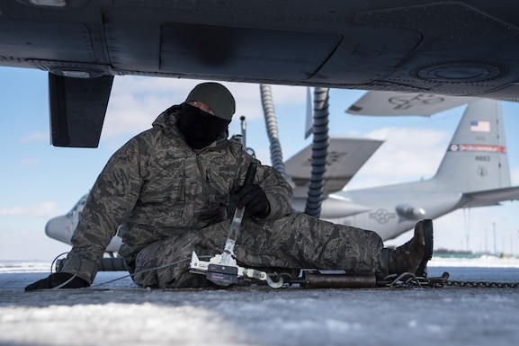 Photo of a military member sitting in the snow, using military equipment to anchor down a C-130 with a C-130 in the background.