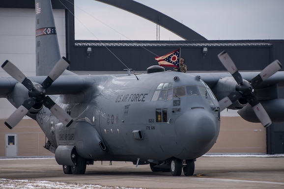 A photo of a C-130 taxiing into a parking space as a military member holds the Ohio flag out of the window.