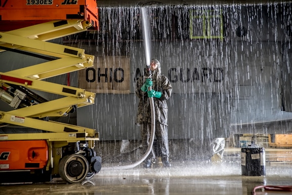 A photo of a military member using a hose to spray water onto a C-130 in the aircraft hanger.