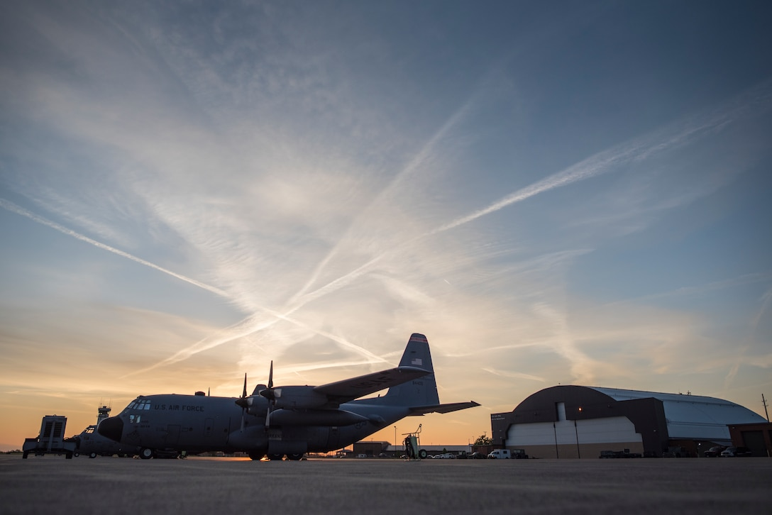 A photo of a C-130 in front of an aircraft hanger during early morning.