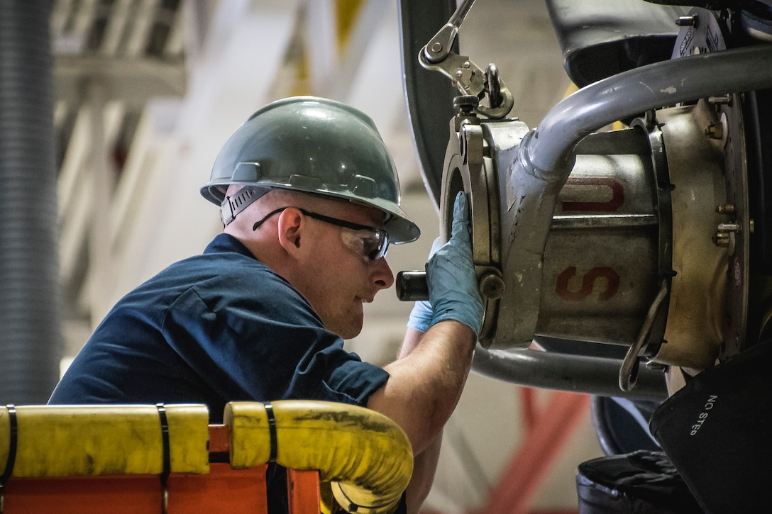 Photo of a military member working on an aircraft engine.