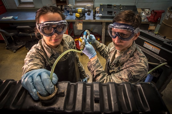 Environmental portrait photo of two military members behind military equipment.