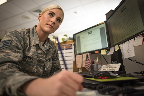 Environmental portrait photo of a military member writing on paper in front of a computer