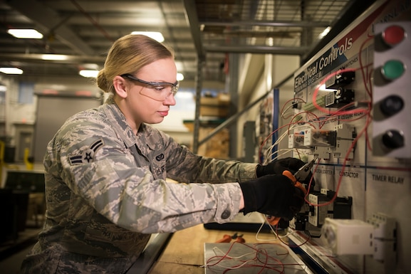 Environmental portrait of a military member posed in front of electrical equipment.