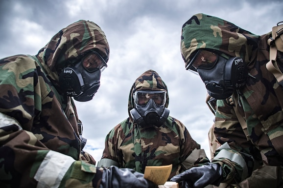 Photo of 3 military members in chemical gear, reviewing chemical papers.