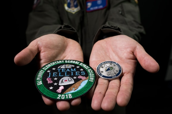 Lt. Col. (Dr.) Peter Lee, a surgeon at the 179th Airlift Wing, Mansfield, Ohio, holds a mission patch and challenge coin Oct. 13, 2018, in a photo studio at the 179th AW. These were designed by elementary school students from Eli Pinney Elementary School in Dublin, Ohio, who participated in a three-month after school program, led by Lee, that taught the students about the space environment and how to design experiments. (U.S. Air National Guard photo by Senior Airman Megan Shepherd)