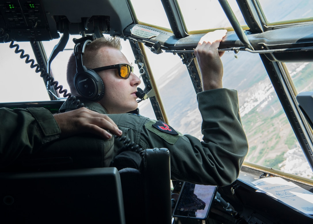 U.S. Air Force Capt. Dan Hill, 37th Airlift Squadron C-130J Super Hercules pilot, looks out his window while copilot over Romania, Aug. 21, 2019. Romanian and U.S. Air Force members participated in exercise Carpathian Fall 2019 allowing U.S. military members stationed at Ramstein Air Base, Germany, the opportunity to attain certifications and training that isn't otherwise possible in Germany. (U.S. Air Force photo by Staff Sgt. Kirby Turbak)