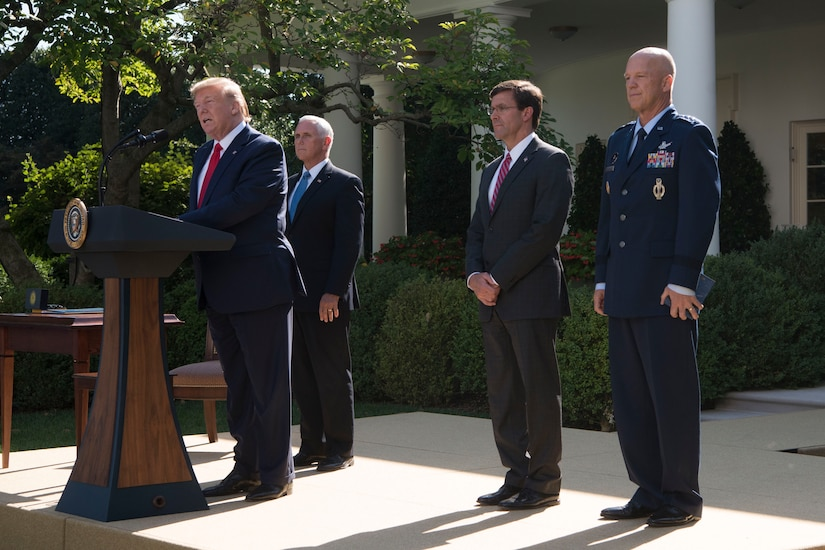 President Donald J. Trump speaks at a podium with two men in suits and an Air Force general standing behind him.