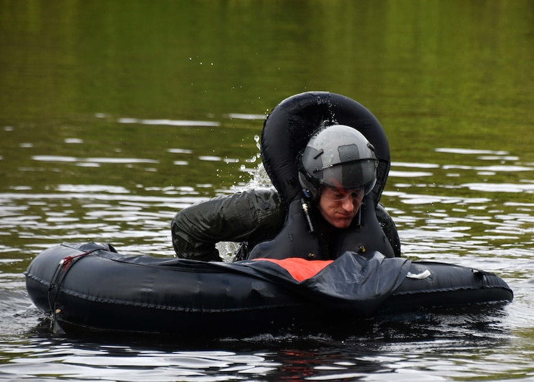 Pilot practices getting into a rescue raft during water survival training
