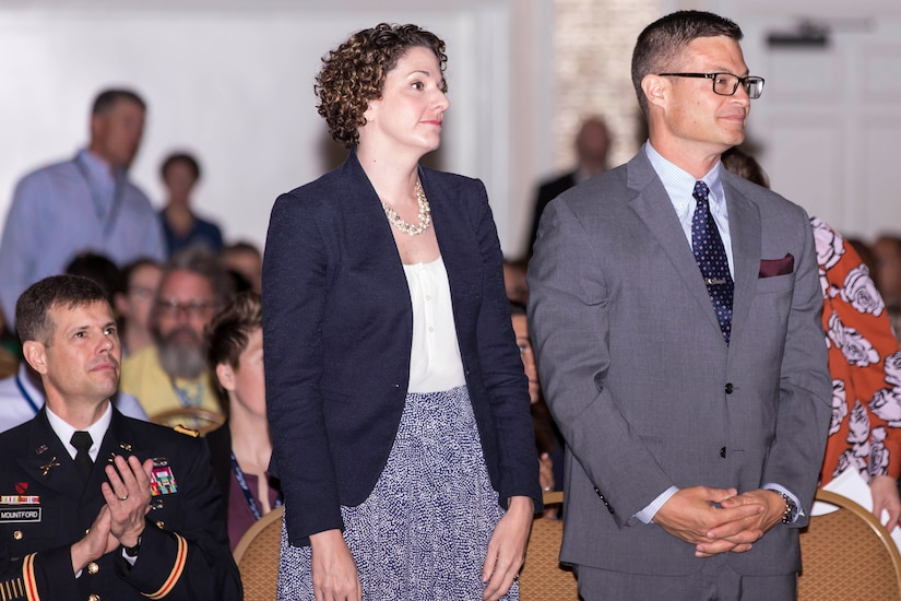A woman and man stand while other sit around.