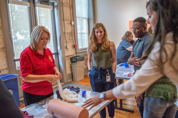"Gina Pickard, Trauma Division manager at Brooke Army Medical Center's Trauma Clinic, shows City of San Antonio council staff members how to pack a wound during Stop the Bleed held at the Plaza de Armas building in downtown San Antonio Aug. 29. The training consisted of a presentation where attendees learned the ""ABCs of Bleeding Control"" along with some hands-on practice in applying tourniquets, packing wounds and applying direct pressure to stop bleeding."