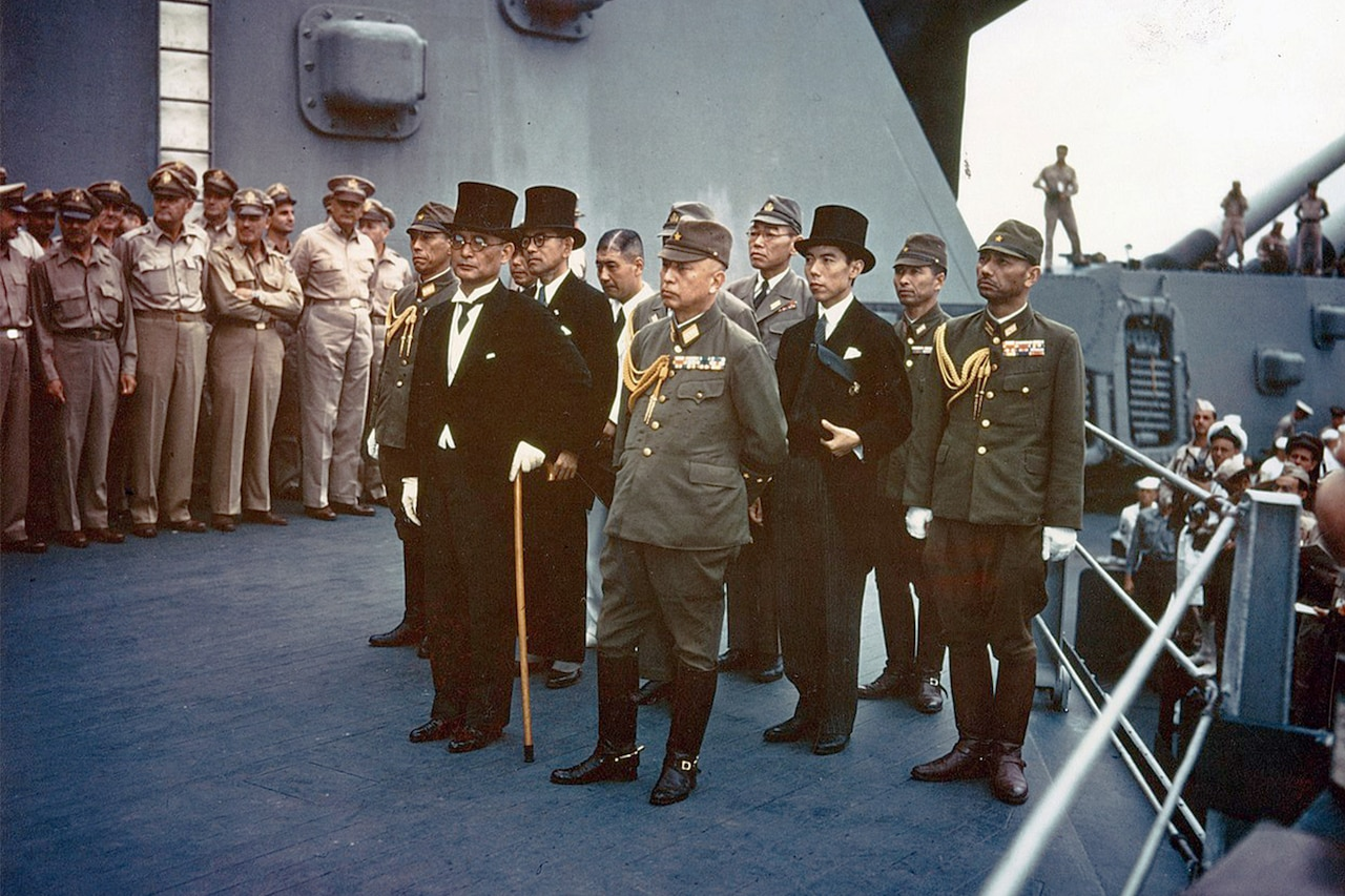 Japanese civilians in formal attire and officers in uniform stand on battleship deck with Allied service members standing nearby.