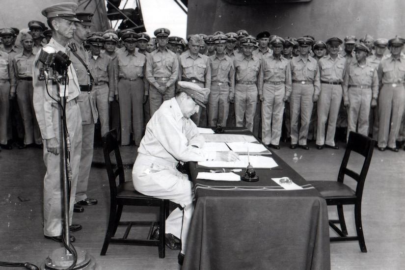 U.S. general signs document as other officers look on.