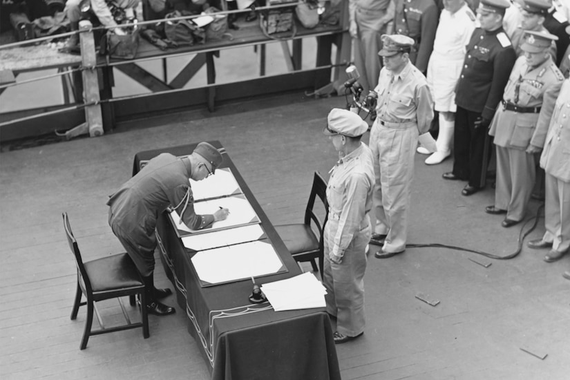 Japanese officer signs document.as Allied officers look on.