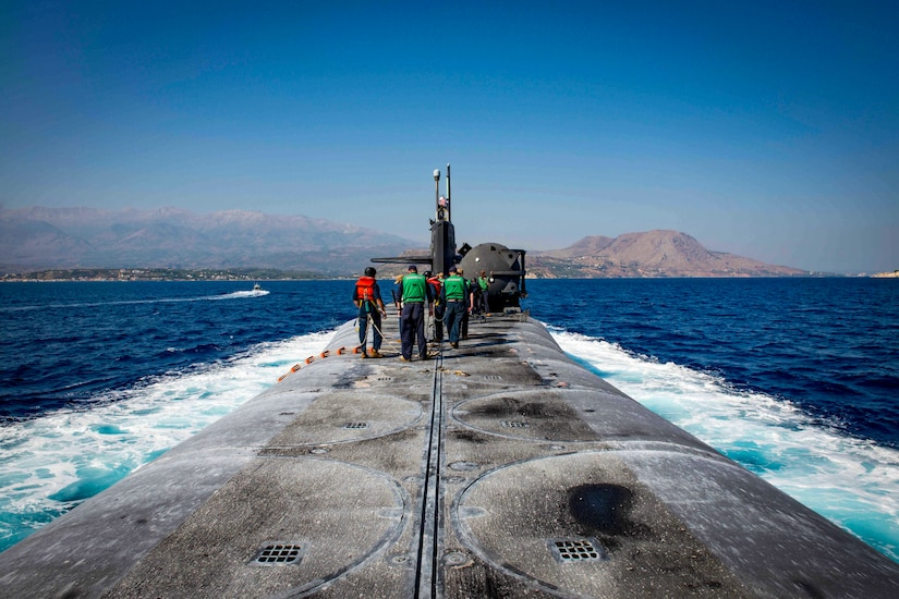 Sailors stand on top of a submarine as it travels through waters.
