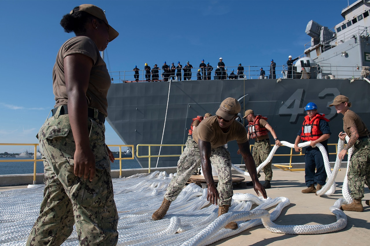 Sailors organize lines of rope on a ship.
