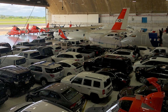 Vehicles are parked in a hangar.