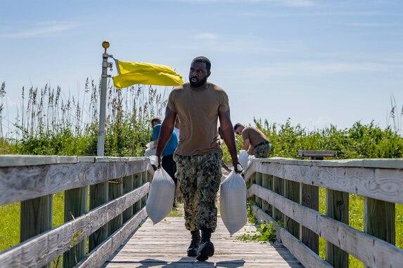 A sailor walks with sandbags.