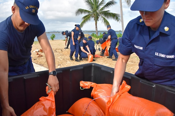 Coast Guard members place sandbags into a container.