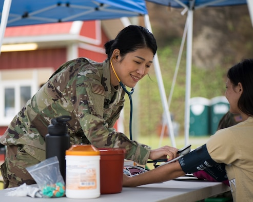 Senior Airman checks a patient's blood pressure